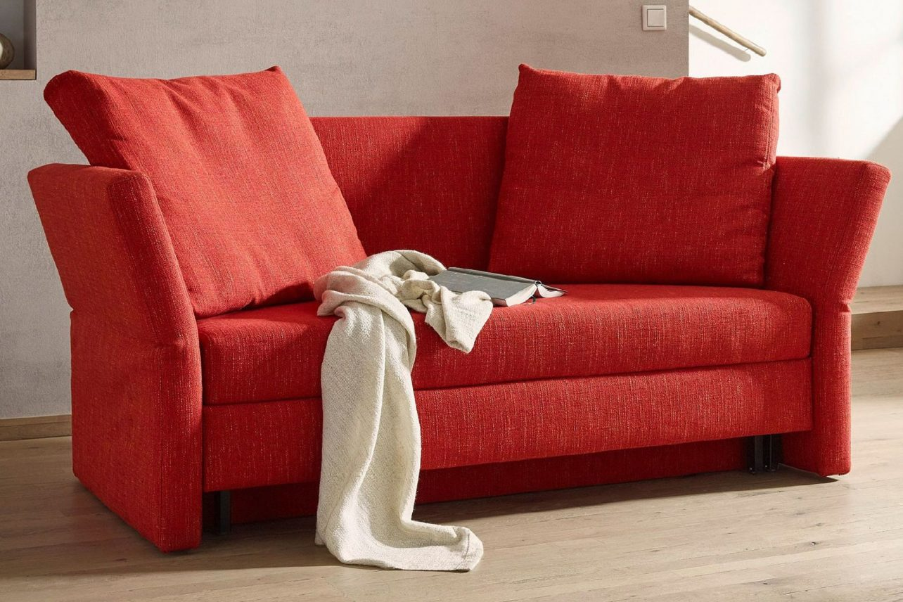 Schlafsofa Cassino in Rot mit klappbaren Armlehnen und soften Rückenkissen.