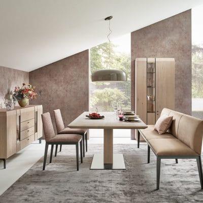Esszimmer Cava mit ausziehbarem Säulentisch in Asteiche massiv, Vitrine, Sideboard, Polsterbank. Ausführung Asteiche gebürstet platinfarben geölt